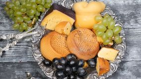 Luxury food concept. Cheese restaurant serving. Food art concept. Variety of hard cheese and branch of grapes on rarity. Silver plate put on wooden board. Top stock video footage