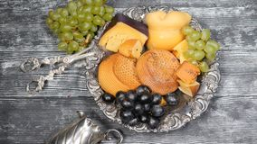 Luxury food concept. Cheese restaurant serving. Food art concept. Variety of hard cheese and branch of grapes on rarity. Silver plate put on wooden board stock footage