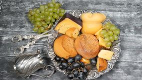 Luxury food concept. Cheese restaurant serving. Food art concept. Variety of hard cheese and branch of grapes on rarity. Silver plate put on wooden board. Top stock video