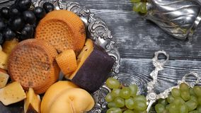 Luxury food concept. Cheese restaurant serving. Food art concept. Variety of hard cheese and branch of grapes on rarity. Silver plate put on wooden board. Top stock footage