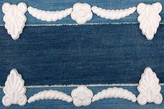 Luxury frame made of white stucco plaster lying on denim. Stock Image