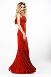 Luxury. Full Length of Elegant Lady in Red Satiny Dress. Frizzy Blond Hair. Woman in Red Satiny Dress. Blonde Hair royalty free stock photography