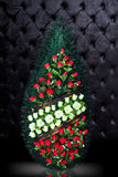 Luxury Funeral wreath with red and white flowers isolated on royal dark background. Royalty Free Stock Images