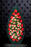 Luxury Funeral wreath with red and white flowers isolated on royal dark background. Stock Images