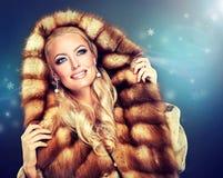 Luxury Fur Coat. Winter model girl in luxury fur coat with a hood Stock Photo