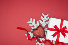 Luxury gift box for holiday event silk wrap snowflake heart. On red background isolated stock photography