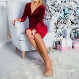 Luxury girl near the Christmas tree in velor red dress royalty free stock photography