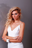 Luxury girl in white dress. Beautiful fashion female model in white dress is posing on gray background Stock Photography