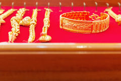 Luxury gold bracelets on red flannel. Stock Photos