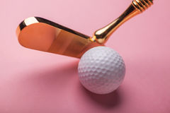 Luxury gold golf club and balls. Head of luxury golden golf club near golf ball on studio pink background Stock Photos