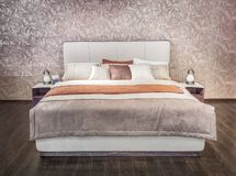 Luxury gray beige modern bed furniture with patterned bed with leather upholstery headboard . Soft brocade fabric bed. Classic modern furniture in home Royalty Free Stock Image