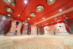 Luxury hall with bright red ceiling and lifts Royalty Free Stock Photo