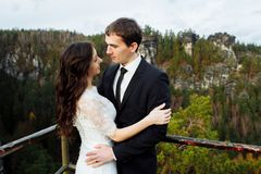 Luxury happy bride and stylish groom hugging each other with tender on background of sunny rocks in amazing mountains royalty free stock images