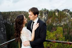 Luxury happy bride and stylish groom hugging each other with tender on background of sunny rocks in amazing mountains stock photography