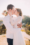 Luxury happy bride and stylish groom kissing on background of sunny mountains Stock Image