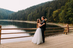 Luxury happy wedding couple bride with bouquet and groom embracing near fence on lake background under sunset Stock Photo