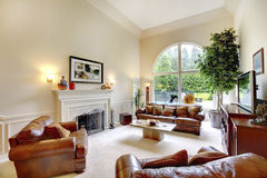 Luxury high ceiling living room interior with fireplace, leather sofas and arched window. Decorated with green tree in a pot Royalty Free Stock Photos