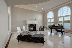 Luxury high ceiling living room with marble floor. Luxury high ceiling living room features beige ivory walls framing large arched windows, traditional fireplace Stock Photo