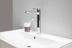 Luxury high faucet mixer and toothbrushes in a glass on a white sink in a beautiful gray bathroom Stock Image