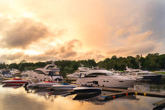 Luxury and high-speed costly yachts and boats at the docks moored to a pier. Luxury and high-speed costly yachts and boats at the docks moored to a pier on a stock photo