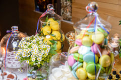 Luxury holiday decoration with desserts, candy, lemon, macaroon. Elegant and luxurious dessert buffet with sweets, cookies, meringues, lemon, colorful macaroon stock images