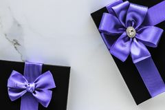 Luxury holiday gifts with lavender silk ribbon and bow on marble background. Wedding present, shop sale promotion and anniversary celebration concept - Luxury royalty free stock photos