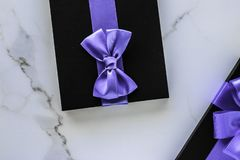 Luxury holiday gifts with lavender silk ribbon and bow on marble background. Wedding present, shop sale promotion and anniversary celebration concept - Luxury stock image
