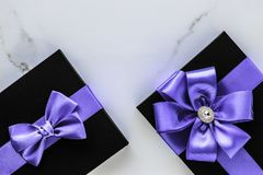 Luxury holiday gifts with lavender silk ribbon and bow on marble background. Wedding present, shop sale promotion and anniversary celebration concept - Luxury stock photos