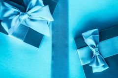 Luxury holiday gifts with silk ribbon and bow on blue background. Baby shower presents, wedding decoration and birthday anniversary concept - Luxury holiday stock images