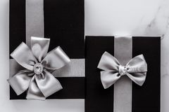 Luxury holiday gifts with silver silk ribbon and bow on marble background. Present for him, shop sale promotion and anniversary celebration concept - Luxury stock images