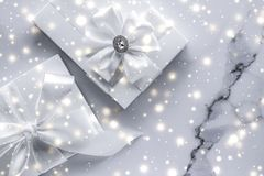 Luxury holiday gifts with white silk bow and ribbons on marble background, Christmas time surprise. New Years Eve celebration, winter decoration and Valentines stock images