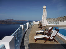 Luxury holidays on Santorini. Terrace with turquoise-colored swimming pool, sun loungers and sun parasols. Fantastic panoramic view of the Aegean sea level with stock photos