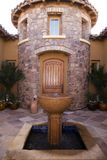 A luxury home. A courtyard entrance to a luxury home with fountain detail in foreground Stock Photos