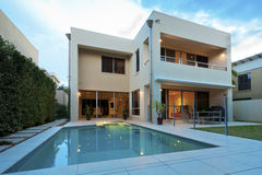 Luxury home. Luxurious modern house with swimming pool and backyard Royalty Free Stock Images