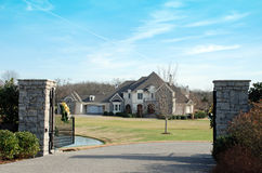 Luxury Home 54.5. A  two-story home on a large lot with a stone fence entrance Royalty Free Stock Images