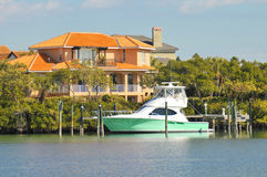 Luxury home and boat on the water Royalty Free Stock Photos