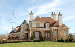 Luxury Home Castle 71. A  two-story home with a stone facade, raised beds and red roof. A electric power line tower in the background Royalty Free Stock Images
