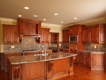 Luxury Home dark wood kitchen. Cabinets and center island Stock Photos