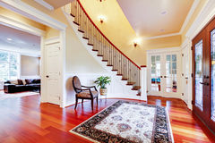 Luxury home entrance with cherry hardwood floor and staircase. Elegant classic design Stock Photos