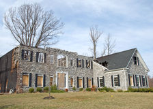Luxury Home Fire Damage 1. What remains of a luxury home with a stone facade.  The roof and attic are gone and the side of the house is charred Royalty Free Stock Photos