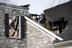 Luxury Home Fire Damage 2. What remains of a luxury home with a stone facade.  The roof and attic are gone and the side of the house is charred Royalty Free Stock Images