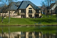 Luxury home on the golf course. A luxury home on the golf course with a man made lake in the foreground royalty free stock photo