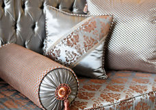 Luxury Home Interior. Luxurious home interior with a couch and pillows upholstered with silks Royalty Free Stock Image