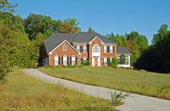 Luxury Home. Large luxury home in a residential development. Appears to be abandoned with overgrown grass and weeds, and it is missing a shutter Royalty Free Stock Photography