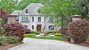 Luxury Home With Open Gate. Large luxury home with a stone covered facade, perfect green grass lawn, fountain with flowers, wood door and a wrought iron gate royalty free stock photos