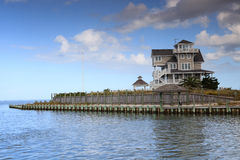 Luxury Home Surrounded by Water. Landscape view of luxury lifestyle home surrounded by the water of Pamlico Sound and Atlantic ocean as seen from the harbor at Stock Image