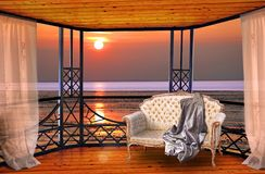 Luxury hotel balcony room with sunset ocean window view