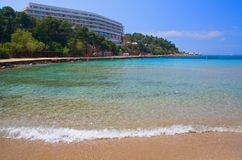 Luxury Hotel Beach. View across bay to luxury hotel in Greece. Gentle wave laps up on beach royalty free stock photos