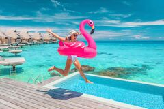 Free Luxury Hotel Beach Vacation Ocean Overwater Bungalows Suite Resort. Happy Woman Tourist Jumping Of Joy In Funny Pool Toy Royalty Free Stock Images - 215389319