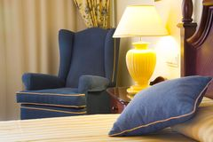 Luxury hotel bedroom. Detail of a luxury hotel bedroom featuring bed, chair and bedside lamp Stock Photos